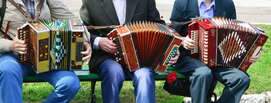 Three people sitting on a bench playing the accordion.