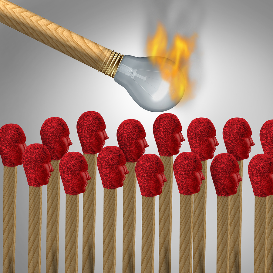 Ideas that catch on concept as a viral marketing symbol and spreading a popular idea or propaganda and social brainwashing communication icon as a lit matchshaped as a light bulb lighting a group of other matches shaped as human heads.