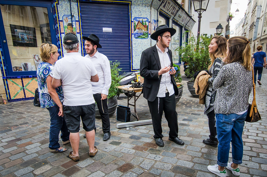 Orthodox Jewish young men reach out to tourists discussing their religious beliefs.