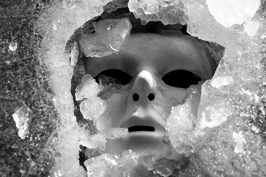 Depressive mask of a human face and ice shards in frosty and winter time