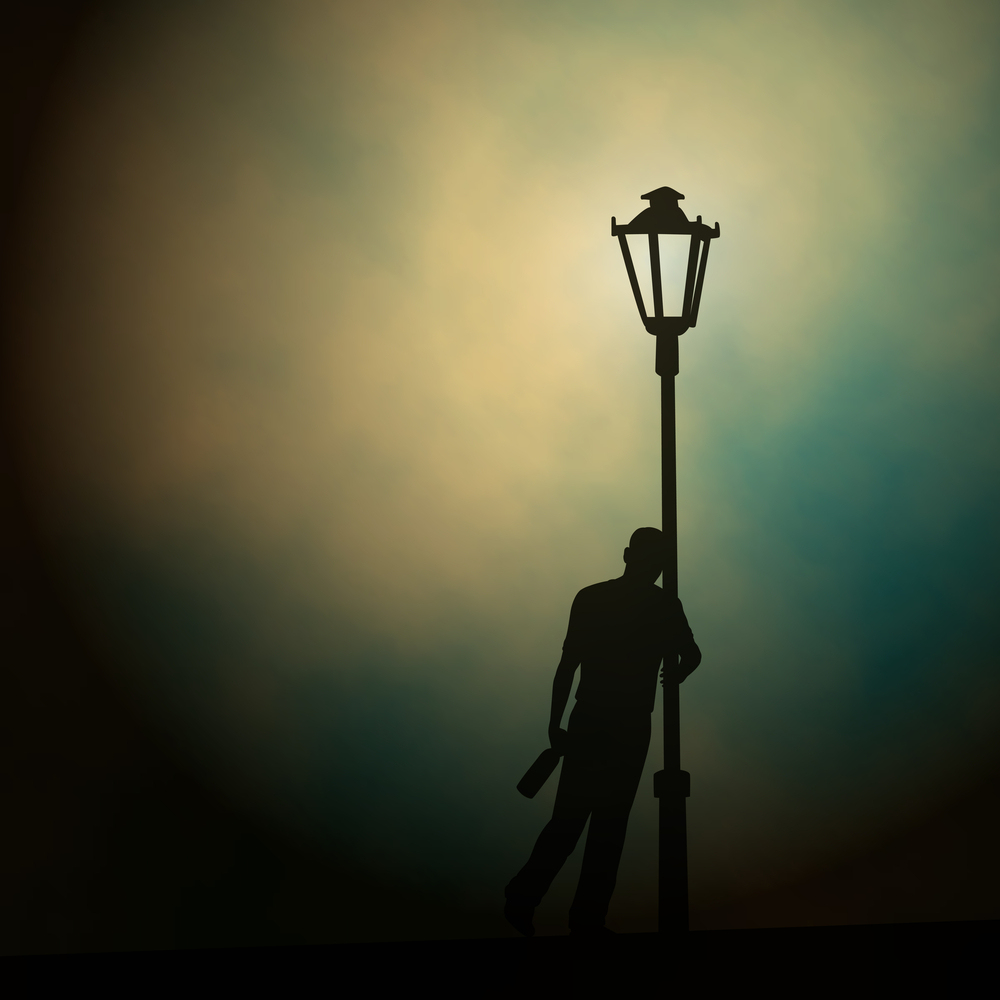A drunken man leaning against a lamp-post at night