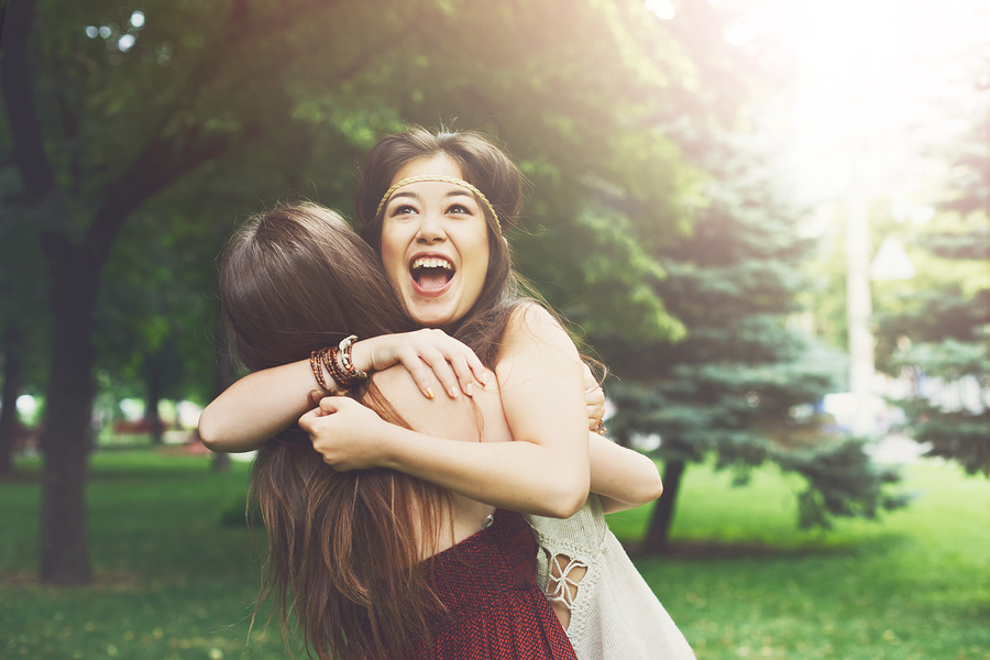 Two happy young girls hug each other. Females embracing, laughing and excited. Woman friendship, walk in the park outdoors.